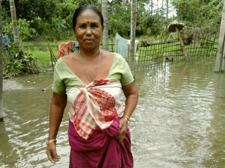 Makita Daw wades through the flood water in front of her home. Photo Credit: Oxfam