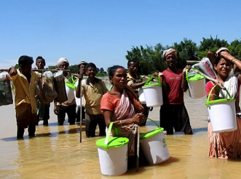 Affected people holding Oxfam buckets