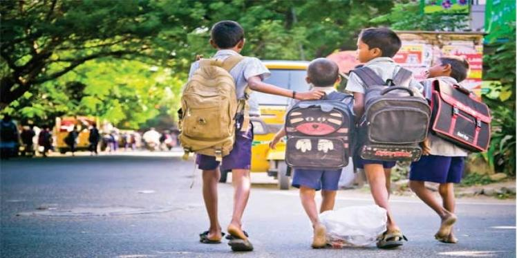 A group of school children walking on the road