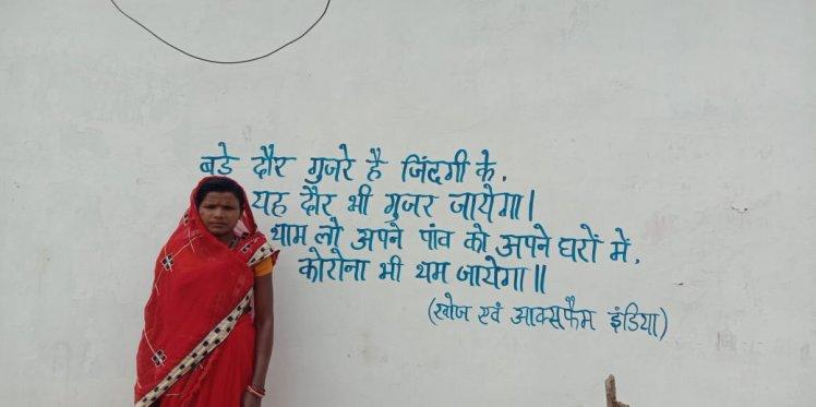 A woman stands next to a slogan on Coronavirus (Korba)