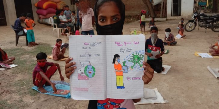 Girl child shows a drawing made during her classes during lockdown